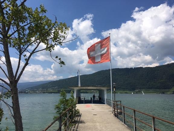 Farbfoto der Schiffsanlegestelle auf der St. Petersinsel im Bielersee, mit Blick auf den See. Im Wind flattert eine Schweizerfahne.