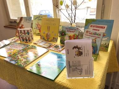 AUf dem Bild sieht man einen Tisch mit einem gelben Tischtuch, auf dem einige Bilderbücher zum Thema Ostern stehen, ausserdem eine breite Glasvase mit Osterzweigen.