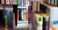 Blick durchs Büchergestell hindurch aufs nächste Gestell