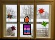 Papierstene und Kerzen verzieren ein Fenster mit Blick auf eine winterliche Landschaft draussen