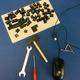 Werkzeuge und eine Maus sowie diverse Tasten einer Tastatur liegen auf einem blauen Hintergrund