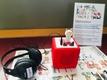 Ein Kopfhörer liegt neben einer roten Toniebox, auf der eine kleine fröhliche Toniefigur steht.