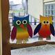 Fensterdekoration in der Bibliothek: 2 Eulen aus bunten Regenbogenkarton sitzen auf einem Ast