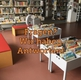 Auf einem Bild von Bilderbuchtrögen im Kinderbereich der Bibliothek, steht mit oranger Schrift: Fragen? Wir haben Antworten!