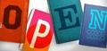 Vier farbige Bücher mit den Buchstaben O P E N liegen nebeneinander