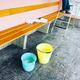 2 farbige Kessel mit Putzwasser stehen vor der Aussenbank